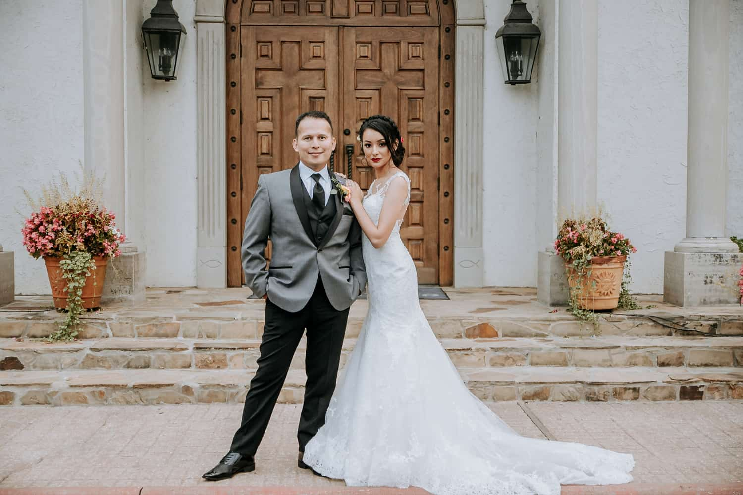 Bride and groom posing in front of the Chapel on the Creeks
