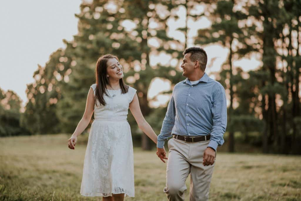 Couple holding hands on their engagement session during sunset hour